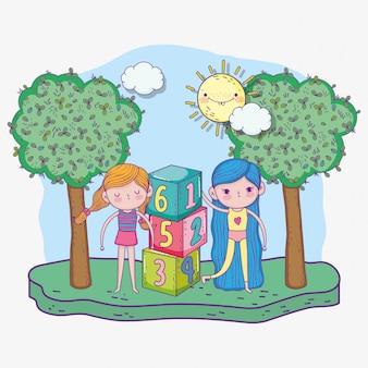 Glücklicher kindertag, niedliche mädchen, die mit zahlenblöcken im park spielen