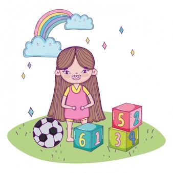 Glücklicher kindertag, süßes mädchen mit blöcken und fußball im gras