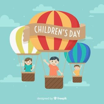 Glücklicher kindertageshintergrund mit kindern in den heißluftballonen