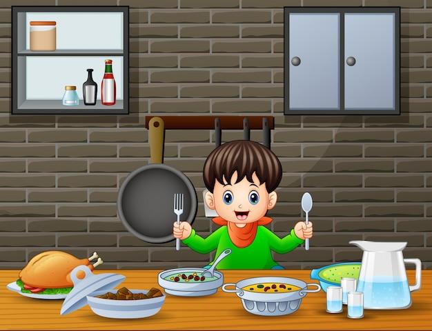Glücklicher kleiner junge, der den löffel und gabel essen am tisch hält