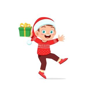 Glücklicher kleiner junge, der geschenk für weihnachten hält