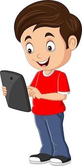 Glücklicher kleiner junge der karikatur, der tablette hält