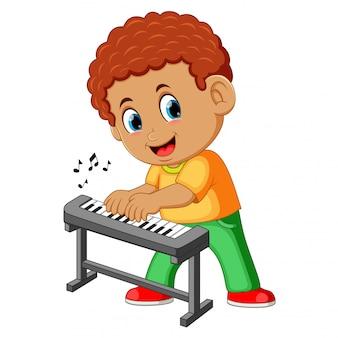 Glücklicher kleiner junge, der klavier spielt