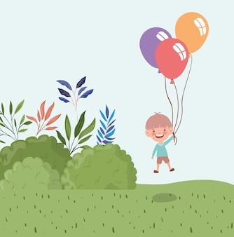 Glücklicher kleiner junge mit ballonhelium in der landschaft