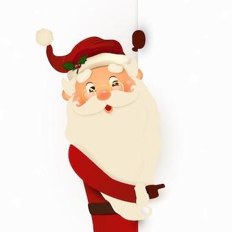 Glücklicher lächelnder weihnachtsmann, der hinter einem leeren schild steht und auf großem leerem schild zeigt.