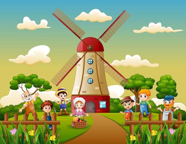 Glücklicher landwirt vor windmühlengebäudehintergrund