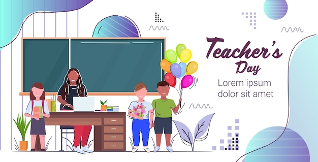 Glücklicher lehrertagfeiertagsfeierkonzeptlehrer, der an schreibtischmischrassenschulkindern sitzt, die blumen und bunte luftballons nahe tafel halten