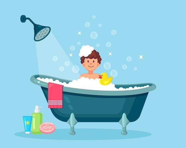 Glücklicher mann, der bad im badezimmer mit gummiente nimmt. waschen sie kopf, haare, körper und haut mit shampoo, seife, schwamm und wasser. badewanne voller schaum mit blasen. hygiene, alltag, entspannung.