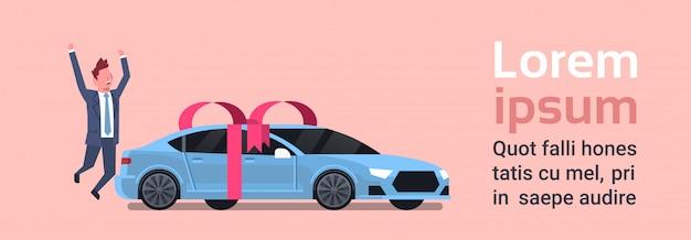 Glücklicher mann-kauf-neuwagen über fahrzeug mit band und bogen. textvorlage