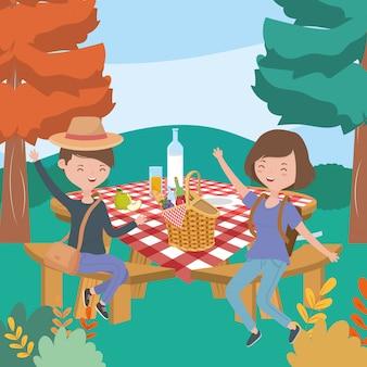 Glücklicher mann und frau mit tabellenlebensmittelpicknicknatur gestalten landschaftlich