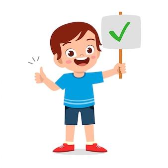 Glücklicher netter junge tragen korrektes zeichen