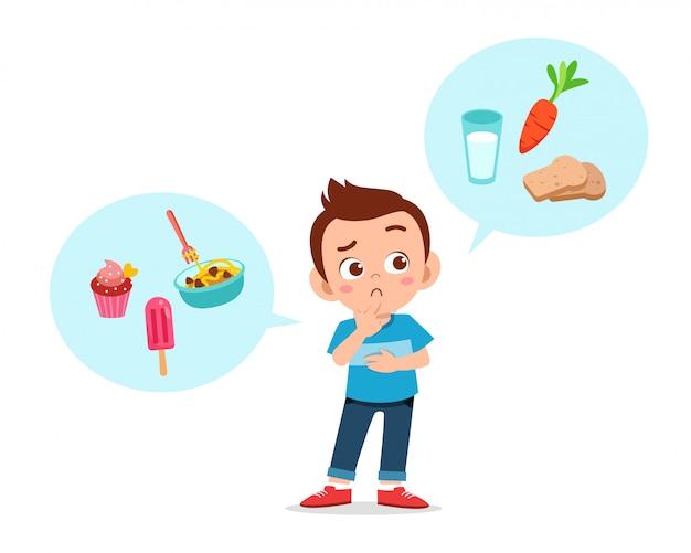 Glücklicher netter kinderjunge denken, lebensmittel zu wählen