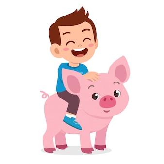 Glücklicher netter kinderjunge, der nettes schwein reitet