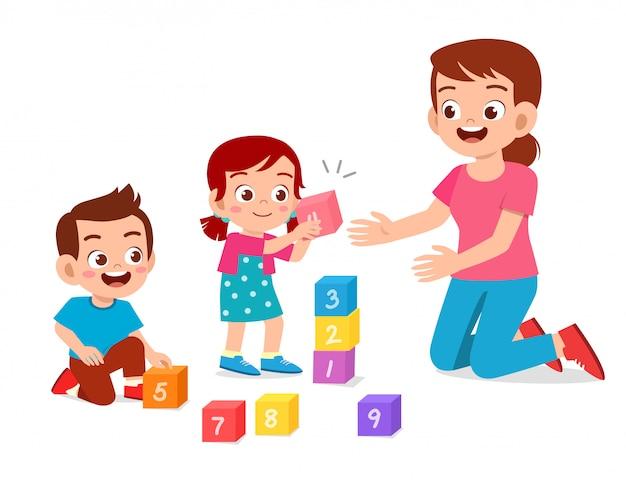 Glücklicher netter kleinkindjunge und -mädchen studieren mit lehrer