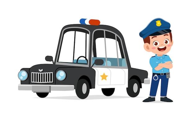 Glücklicher niedlicher kleiner junge, der polizeiuniform trägt und neben auto steht