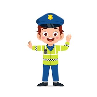 Glücklicher niedlicher kleiner junge, der polizeiuniform trägt und verkehr verwaltet