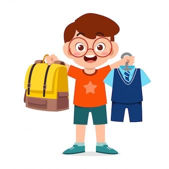Glücklicher niedlicher kleiner junge, der uniform für schule vorbereitet