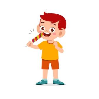Glücklicher niedlicher kleiner junge essen süßigkeiten und süßigkeiten