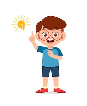 Glücklicher niedlicher kleiner junge mit ideenlampenzeichen