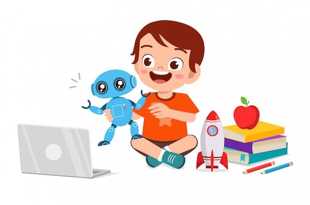 Glücklicher niedlicher kleiner junge spielt computer und roboter