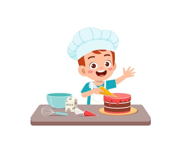Glücklicher niedlicher kleiner junge trägt kochuniform und kocht eine geburtstagstorte