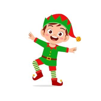 Glücklicher niedlicher kleiner jungejunge und mädchen, die grünes elfenweihnachtskostüm tragen