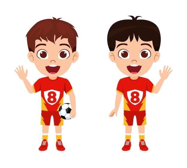 Glücklicher niedlicher kleiner kinderjungencharakter, der fußball mit schönem rotem trikot mit fröhlichem ausdruck lokalisiert und hält