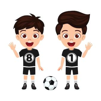 Glücklicher niedlicher kleiner kinderjungencharakter, der mit fußball mit schwarzem trikot mit fröhlichem ausdruck winkt, isoliert