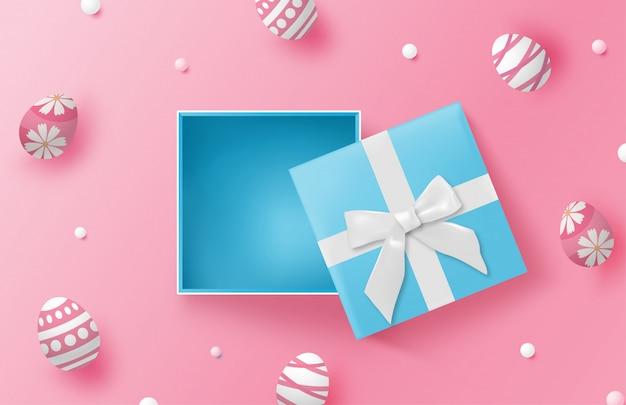 Glücklicher ostertaghintergrund mit ostereiern und blauer geschenkbox auf rosa
