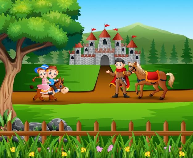 Glücklicher prinz mit den kindern, die ein pferd auf der straße reiten