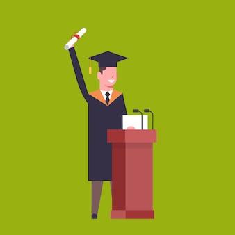 Glücklicher student in graduation cap und kleid standing at tribune hold diploma