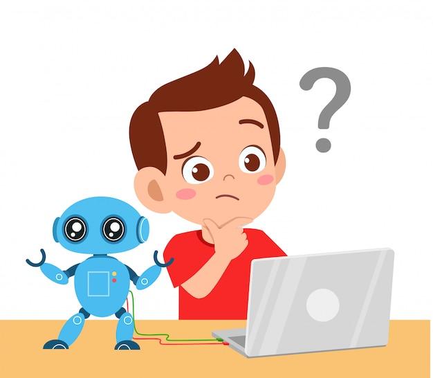 Glücklicher süßer kleiner junge benutzt laptop, wird verwirrt