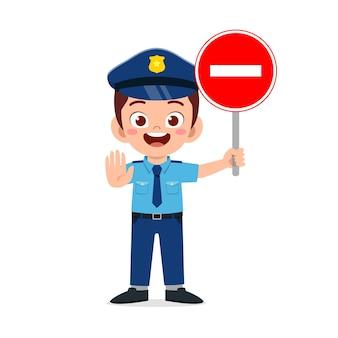 Glücklicher süßer kleiner junge, der polizeiuniform trägt und stoppschild hält