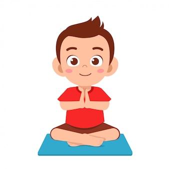 Glücklicher süßer kleiner junge praktiziert yoga
