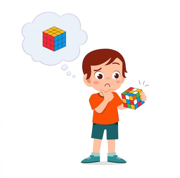 Glücklicher süßer kleiner junge spielt rubikwürfel