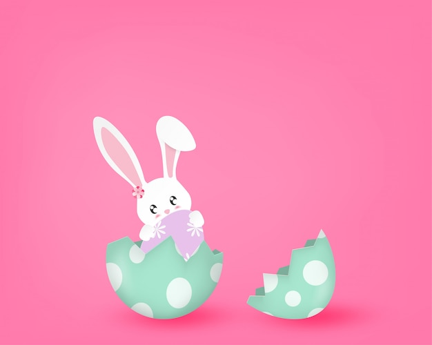 Glücklicher tag mit nettem häschen in einem halben gebrochenen ei auf rosa