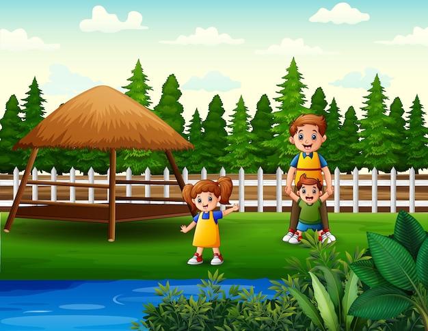 Glücklicher vater und seine kinder, die in der parklandschaft spielen