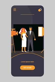 Glückliches frisch verheiratetes paar, das hochzeitsfoto auf mobiler app nimmt