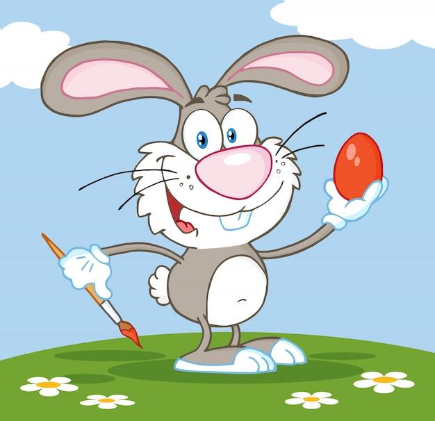 Glückliches graues kaninchen, das osterei malt