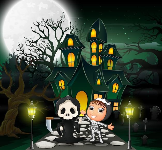 Glückliches halloween-kostümkind vor dem geisterhaus