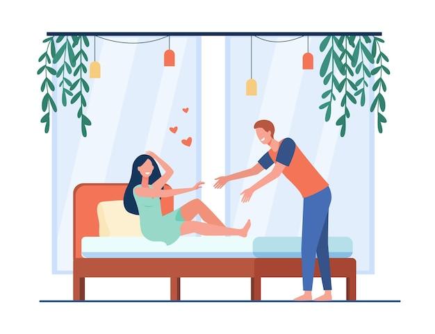 Glückliches junges paar, das im schlafzimmer flirtet