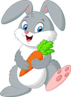 Glückliches kaninchen, das karotte hält