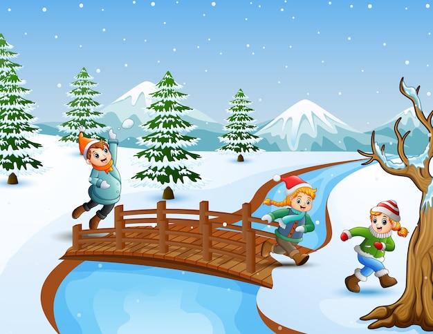 Glückliches kind auf der brücke im schneienden hügel
