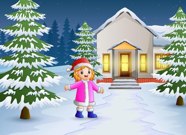 Glückliches kind, das vor dem schneienden haus spielt