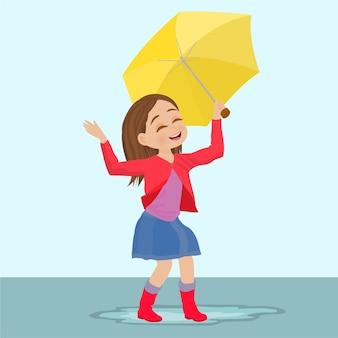 Glückliches kindermädchen mit einem regenschirm und gummistiefeln in der pfütze