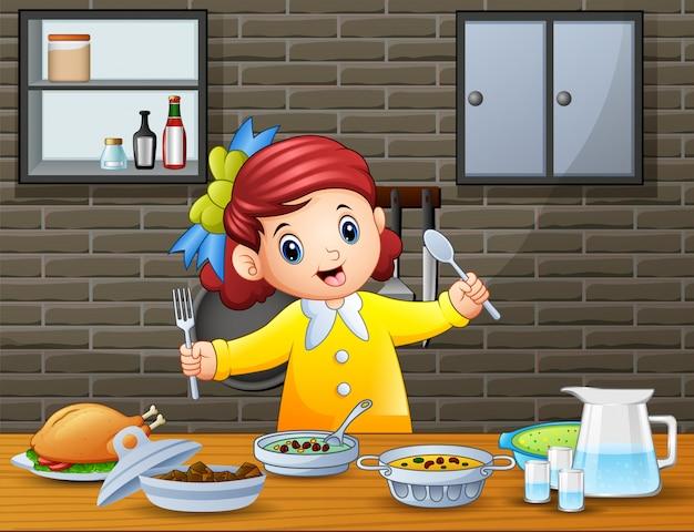 Glückliches kleines mädchen, das den löffel und gabel essen am tisch hält