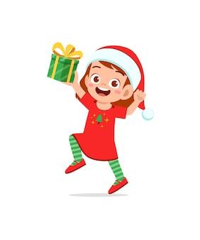 Glückliches kleines mädchen, das geschenk für weihnachten hält
