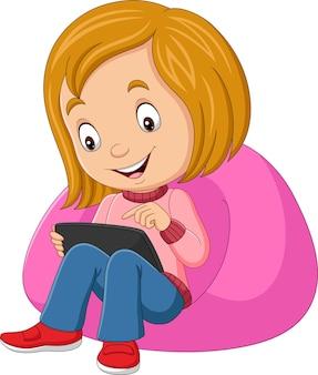 Glückliches kleines mädchen der karikatur, das tablette auf sofa verwendet