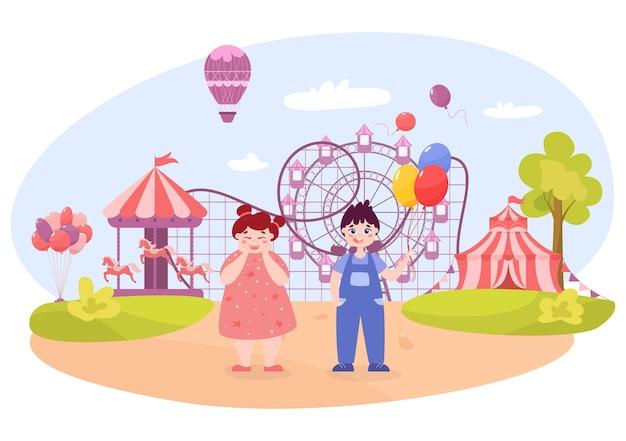 Glückliches kleinkind im vergnügungspark. babyjunge mit luftballons und mädchen im rosa kleid, das nahe attraktionen wie karussell mit pferden, riesenrad, achterbahn steht.