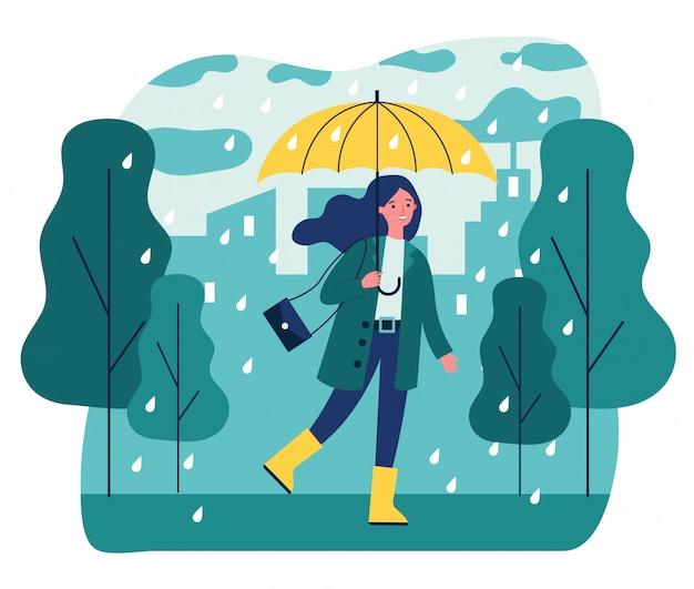 Glückliches lächelndes mädchen mit regenschirm, der im regnerischen tag geht